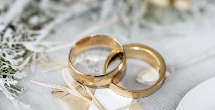 two gold wedding bands on a white background